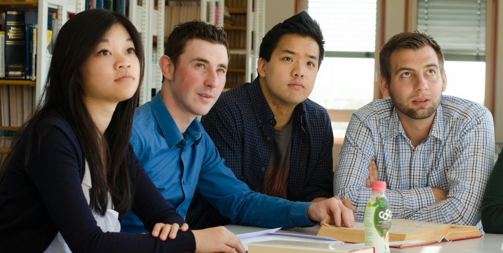 Vier Studierende sehen sich einen Vortrag an